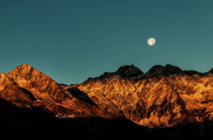 A photo of the moon above golden colored mountains.