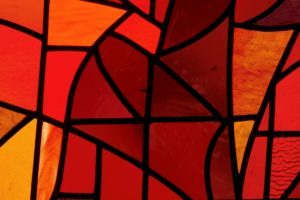 A photo of red and orange stained glass.