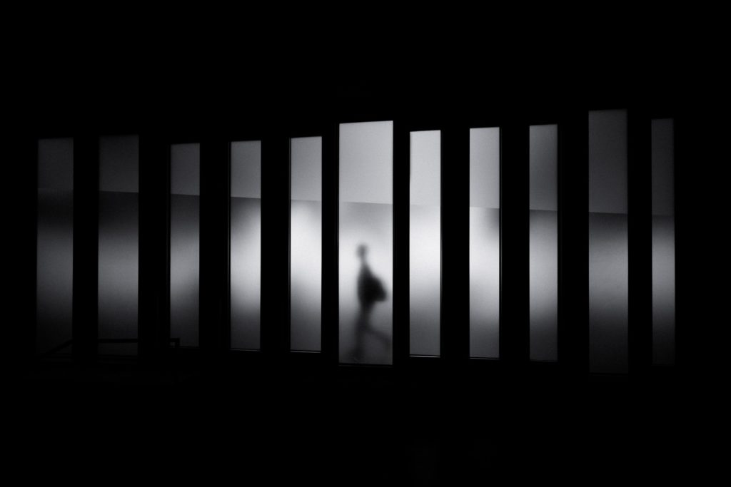 A black and white image of a man reflected through illuminated panels.