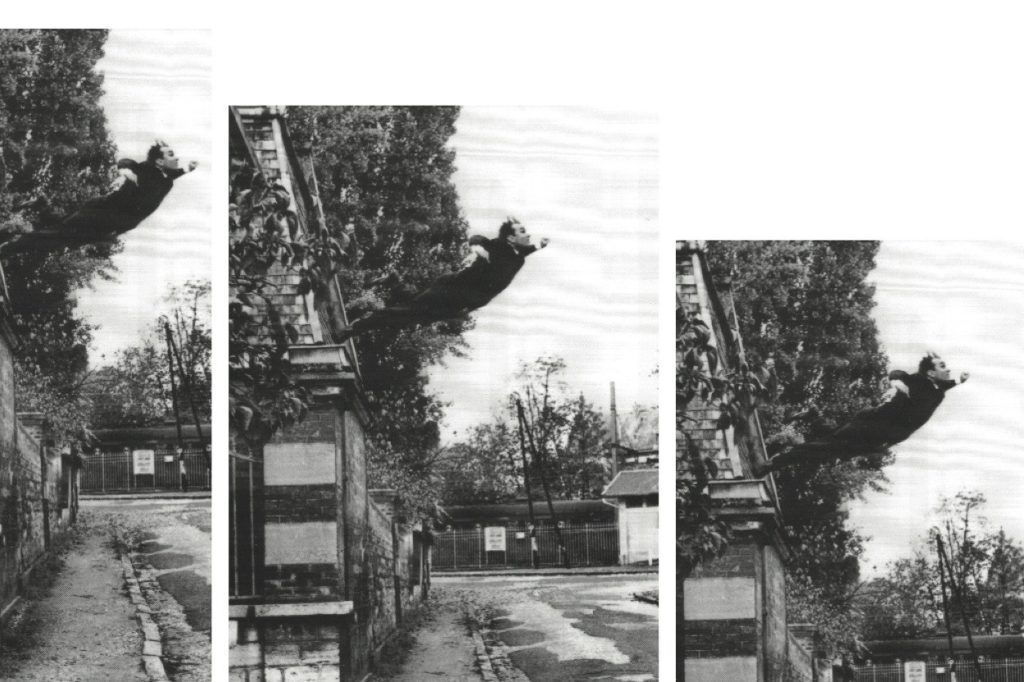 A photo of a man leaping from a roof.