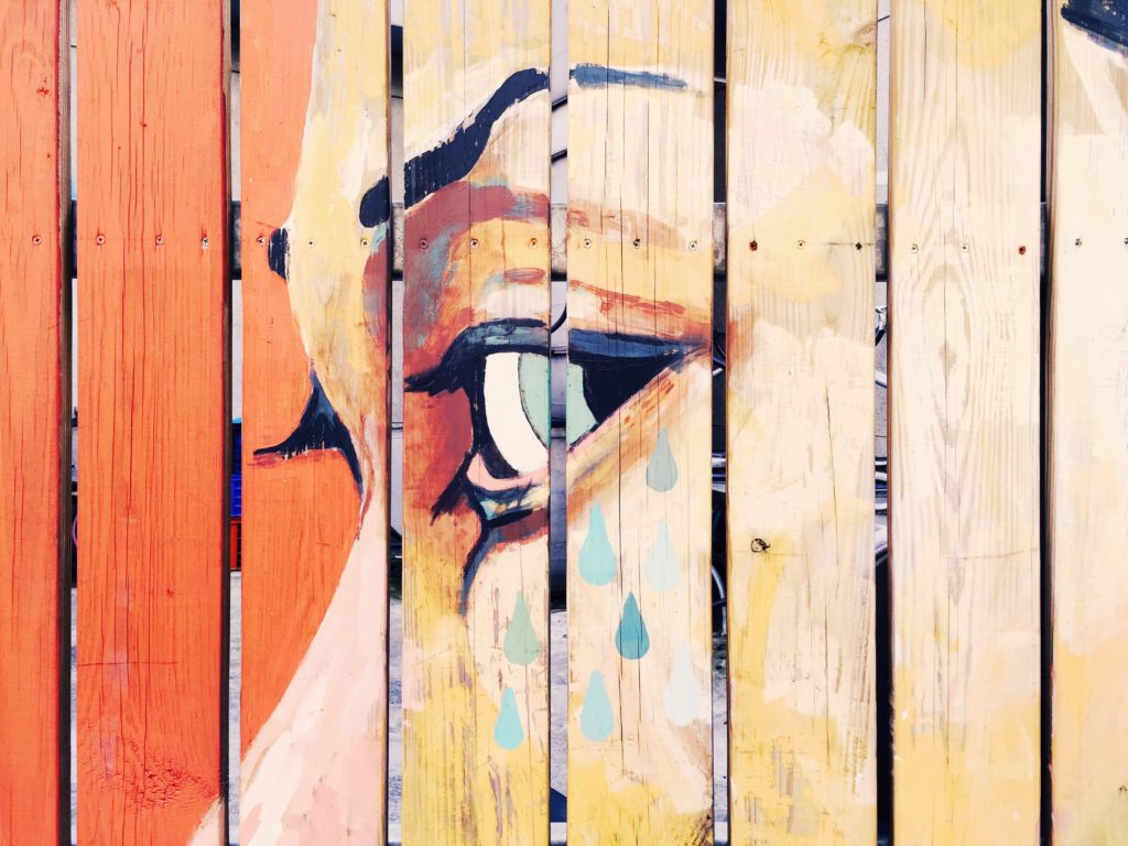 A painted fence depicting the face of a woman.