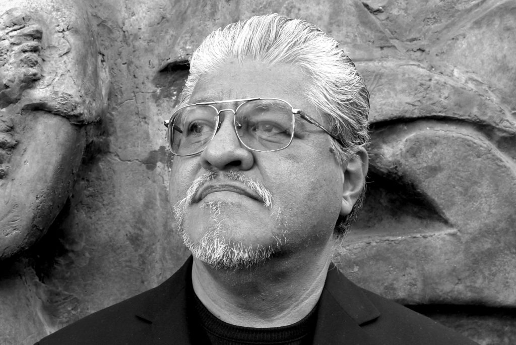 Author photo of Luis Rodriguez in front of a rock wall.