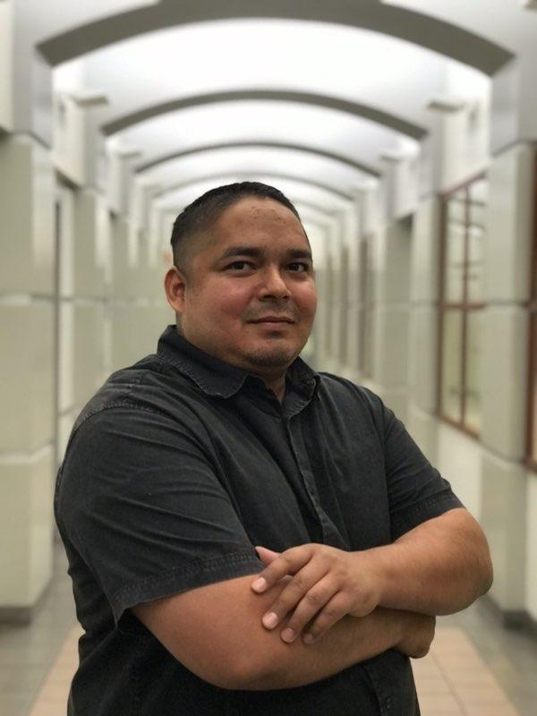 Jose Hernandez Diaz stands in a hallway with his arms crossed.