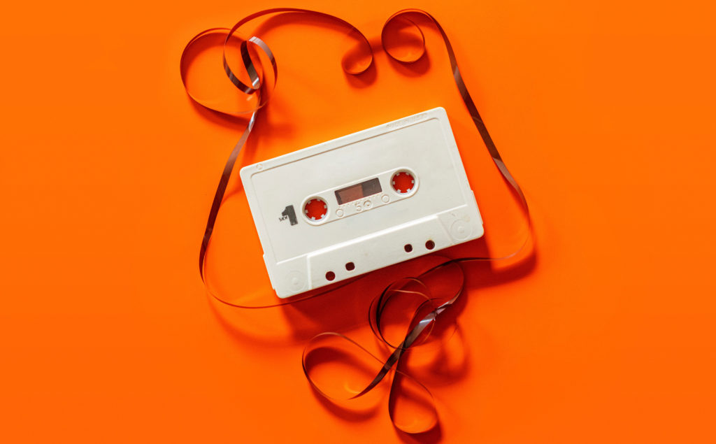 A cassette tape unravelled on an orange background.