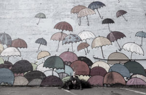 Author photo of Abby Murray. She sits against a mural with an assortment of rainbow umbrellas.