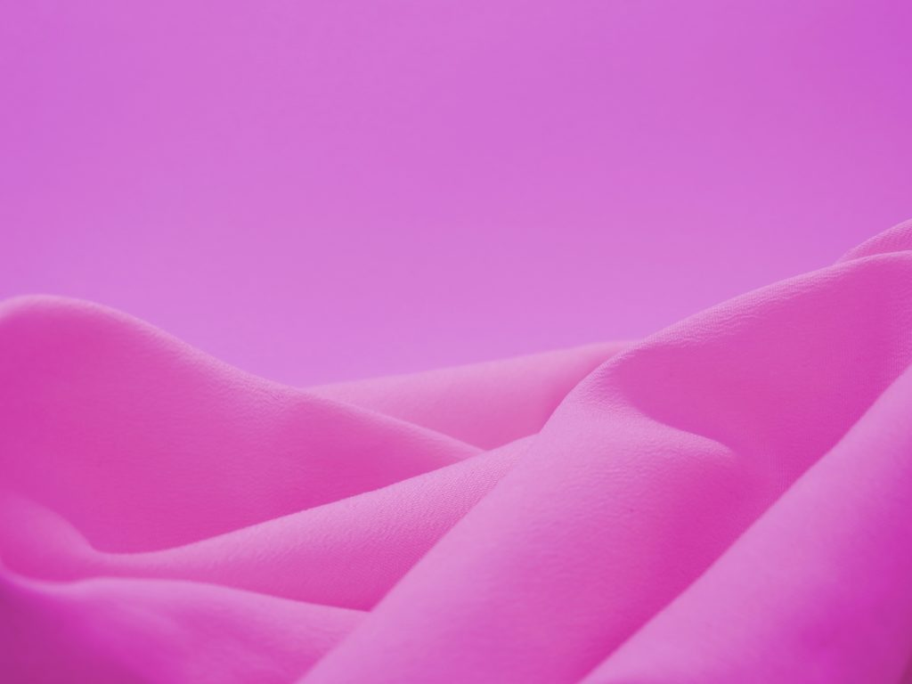 Pink fabric piled against a pink background.